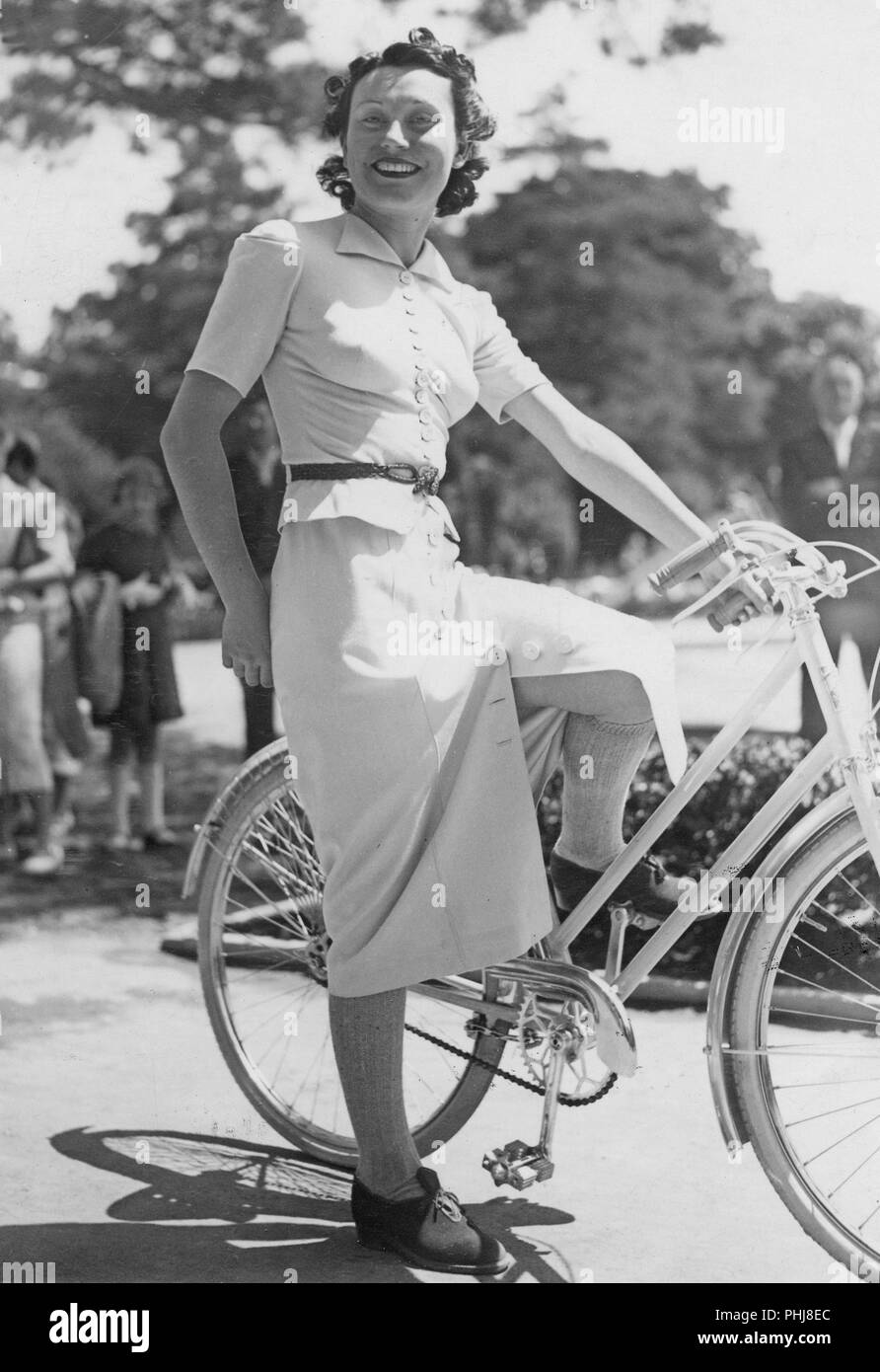1930 Frau auf einem Fahrrad. Eine lächelnde junge Frau auf einem Fahrrad Frauen an einem sonnigen Tag. Schweden 1930 Stockbild