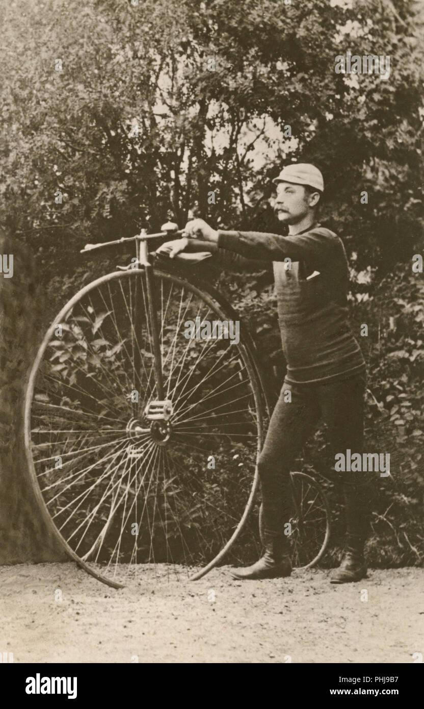 Penny Farthing Fahrrad. Ein Mann steht neben einem penny-farthing Fahrrad. Eine bicycycle Modell mit einem großen und einem kleinen Vorderrad Hinterrad. Schweden 1880 Stockbild