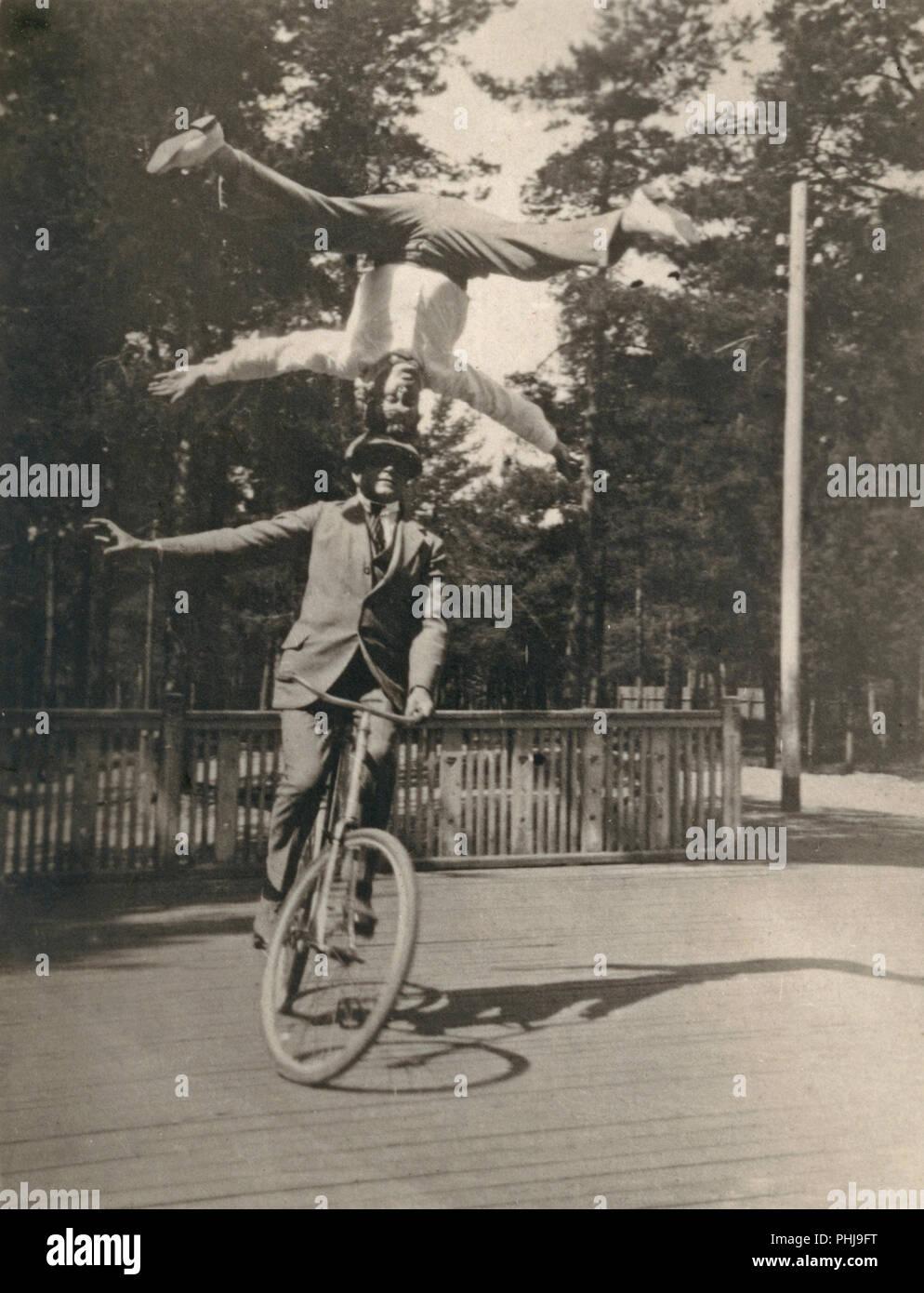 1920er Jahre Männer auf einem Fahrrad. Die schwedische Fahrrad acrobat Fritiof Malmsten führt seine Balance Akt mit seiner jungen Bruder Helge. Eine beeindruckende Leistung, wo er auf seinen Kopf ist und nicht mit den Händen, sein Gleichgewicht zu halten. Fritiof Malmsten wurde zu einem international bekannten Fahrrad Acrobat. Stockbild