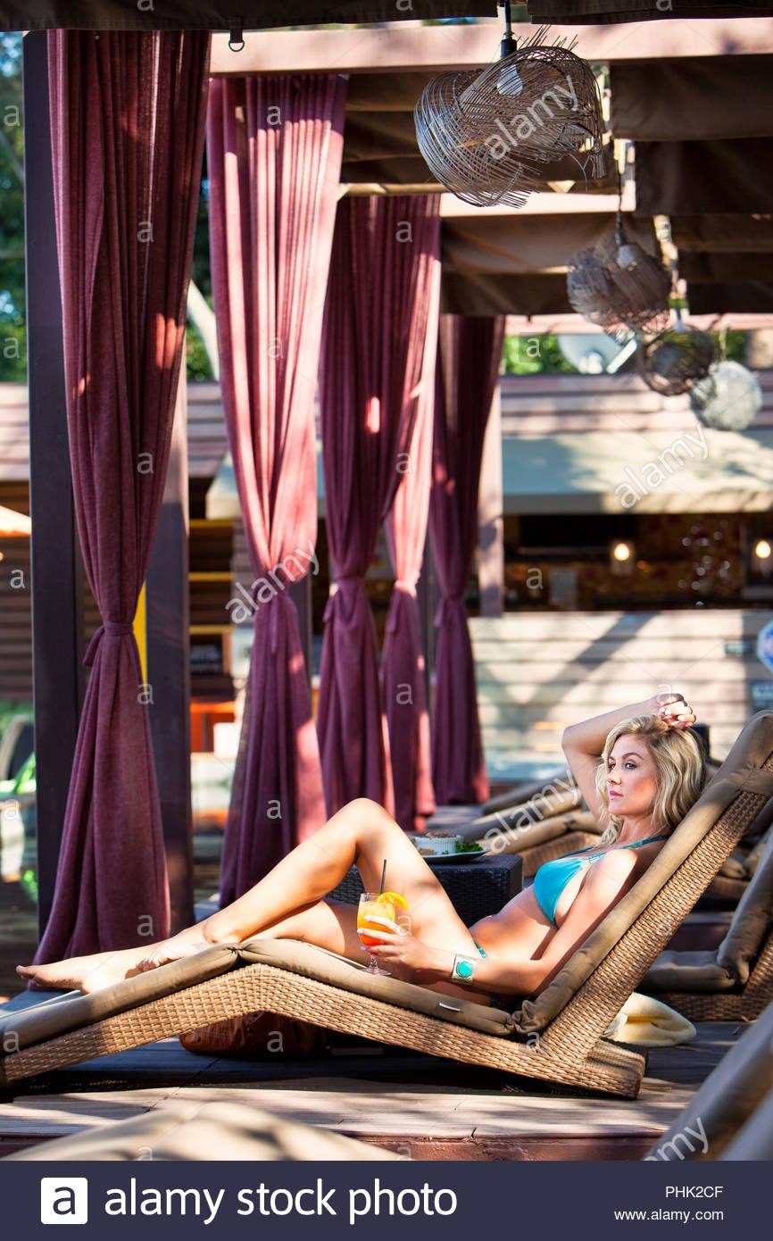 Junge Frau in Bikini holding Saft auf Sonnenliege Stockbild