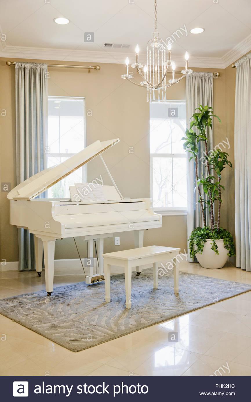 Weißes Klavier unter Kronleuchter Stockbild