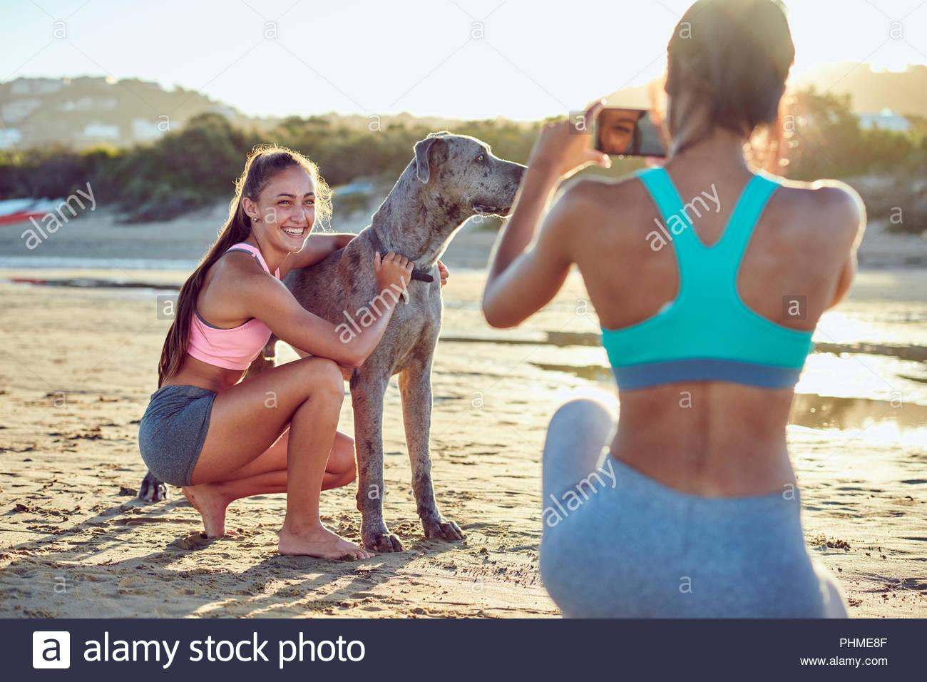Junge Frau Streichelzoo Hund, während ihr Freund Foto dauert Stockbild