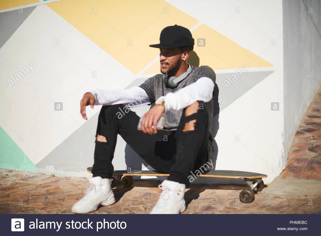 Junger Mann mit tragbaren Lautsprecher sitzen auf Skateboard Stockbild