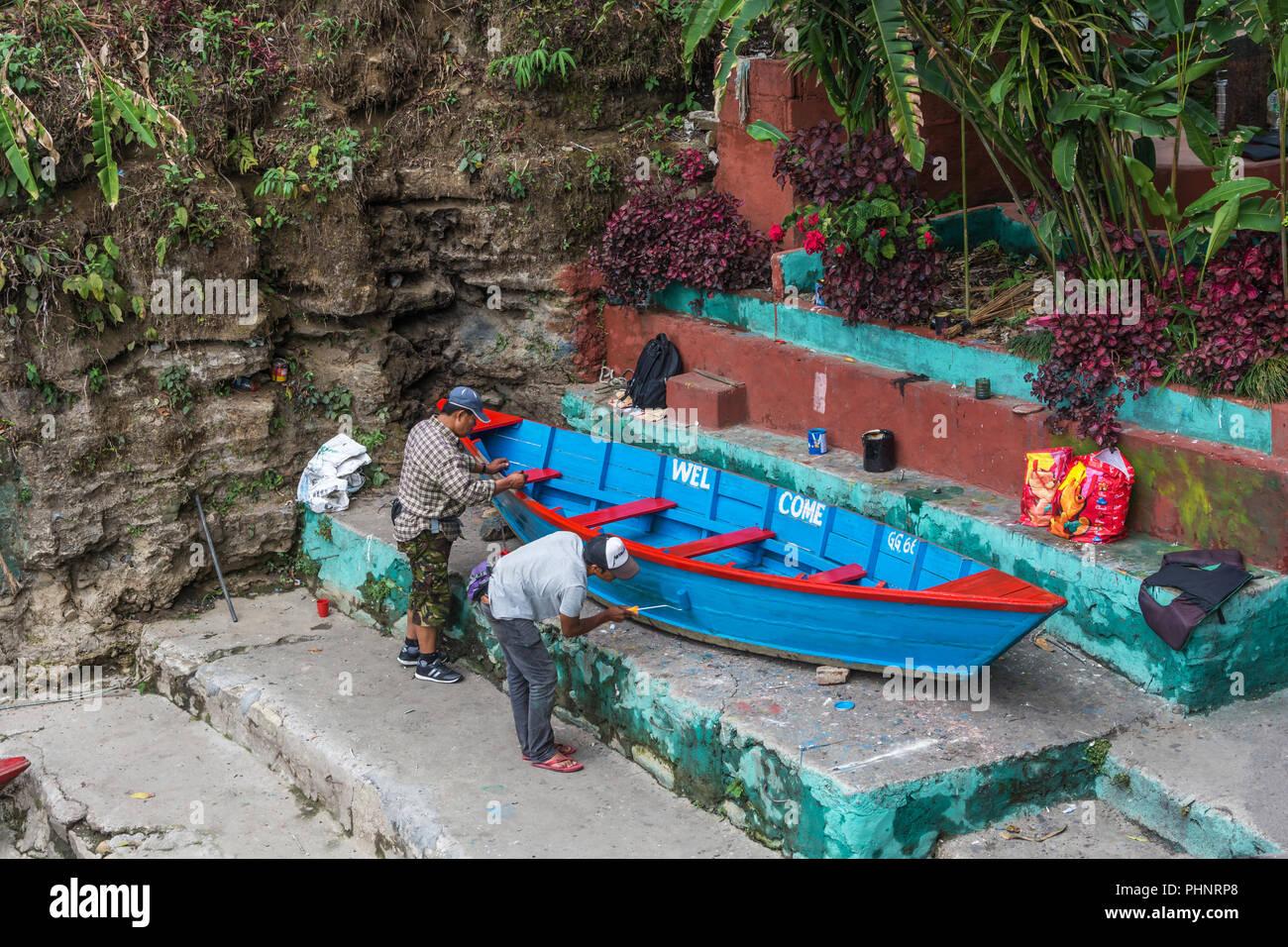 Pokhara, Nepal -11.04.2018: Zwei Arbeiter malen ein holzboot am 11. April 2018 in Pokhara, Nepal. Stockbild