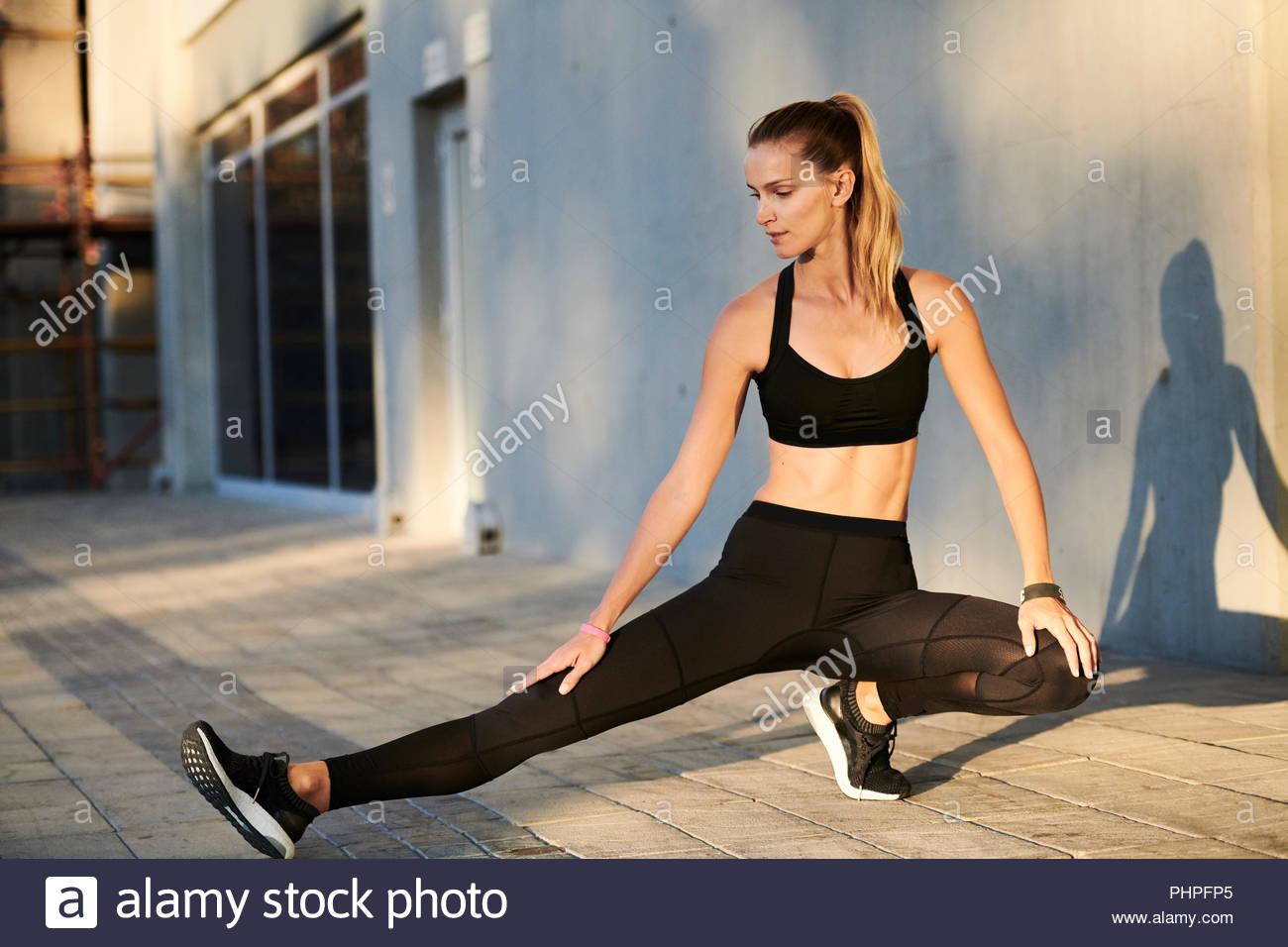 Frau mit schwarzen Sportswear Stretching Stockbild