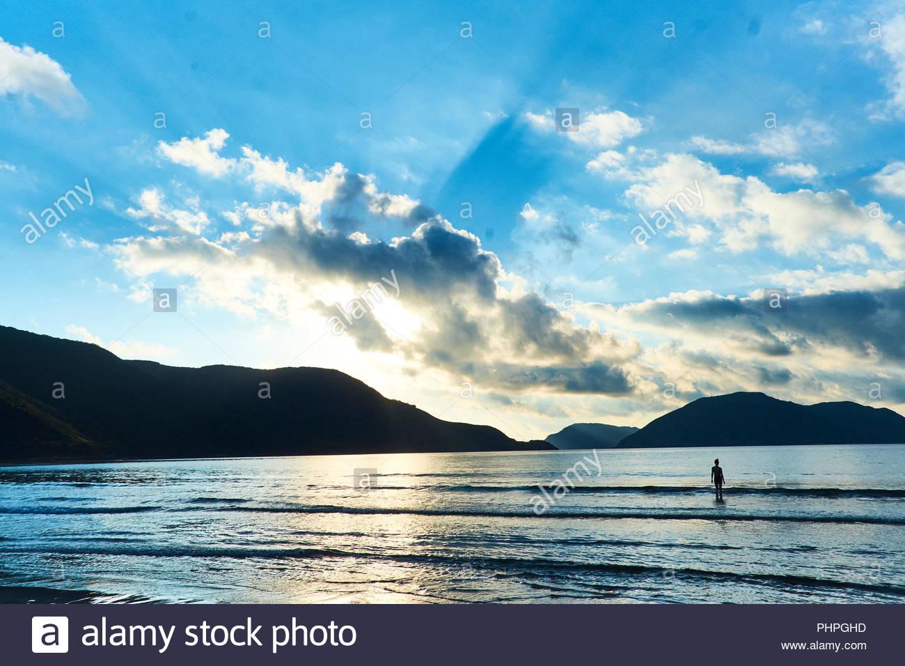 Silhouette der Frau am Strand bei Sonnenuntergang Stockbild