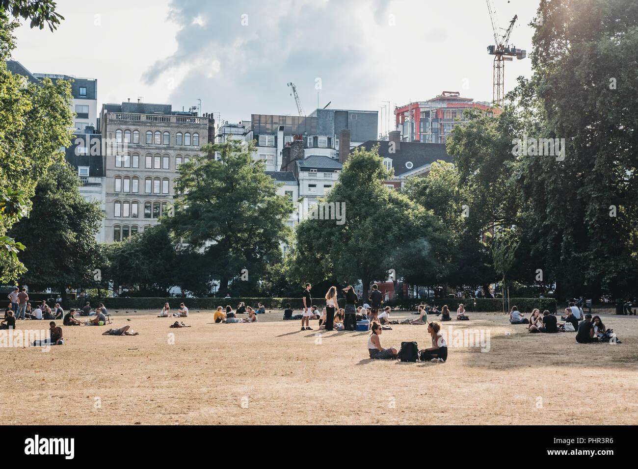 London, Großbritannien - 24 Juli, 2018: die Menschen entspannen in Lincoln's Inn Fields Hitzewelle im Sommer 2018 in London, Großbritannien. Lincoln's Inn Fields ist der größte Pub Stockfoto