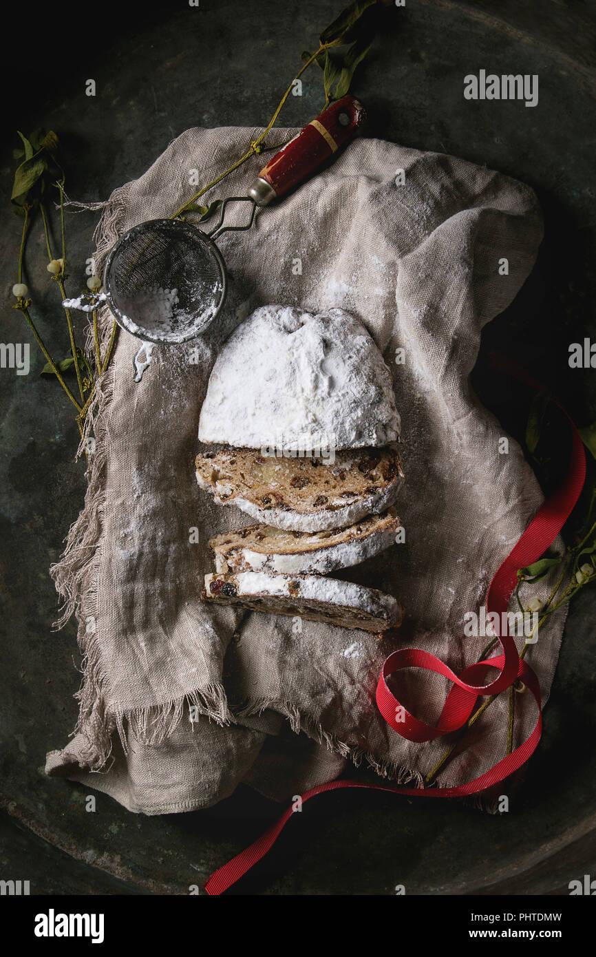 In Scheiben geschnitten Christmas Cake, traditionelle deutsche Festliches backen. Vollkorn Stollen mit Rosinen und Zucker Pulver auf Leinen Serviette mit Sieb, red ribbon, Mis Stockbild