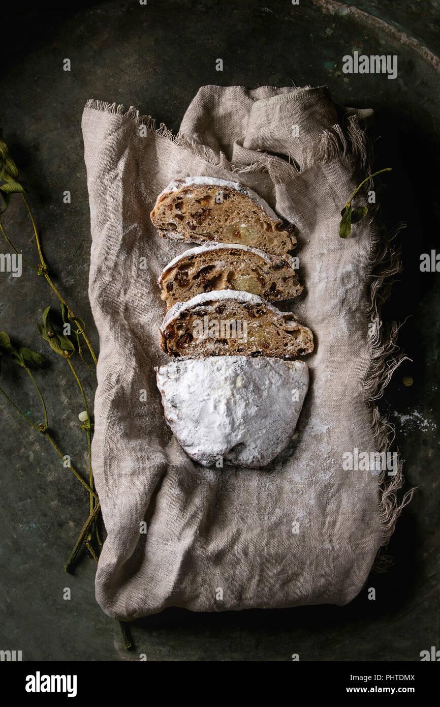 In Scheiben geschnitten Christmas Cake, traditionelle deutsche Festliches backen. Vollkorn Stollen mit Rosinen und Zucker Pulver auf Leinen Servietten mit Zweigen von Mistel Stockbild
