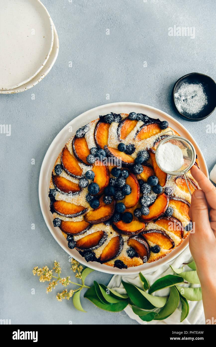 Eine Frau sichten Puderzucker auf einen Pfirsich Kuchen mit blaubeeren fotografiert auf einem grauen Hintergrund von oben ansehen. Grüne Blätter, einen schwarzen Schüssel mit powde Stockbild