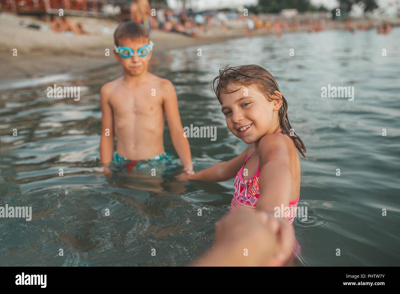 Glückliche Kinder spielen im Meer. Kinder halten sich an den Händen und ihre Mutter einladen, mit ihnen zu gehen. Sommer Urlaub und gesunden Lebensstil Konzept Stockbild