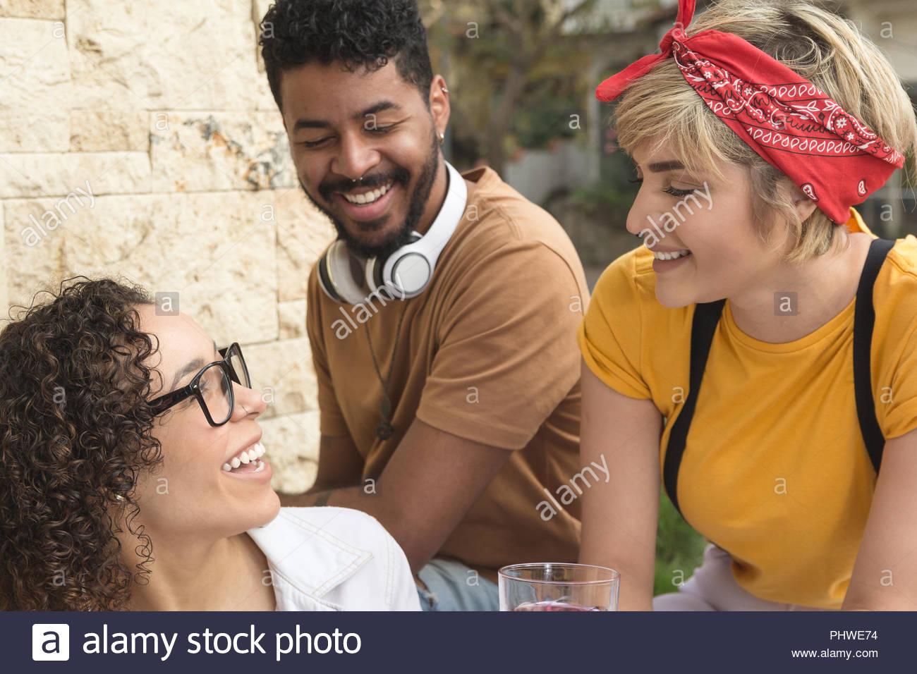 Fröhlicher junger Freunde lächelnd und sitzen im Restaurant außerhalb. Gruppe von Menschen, die gemeinsam Spaß haben im Cafe Bar im Freien. Frühling, warm, Zweisamkeit Stockbild