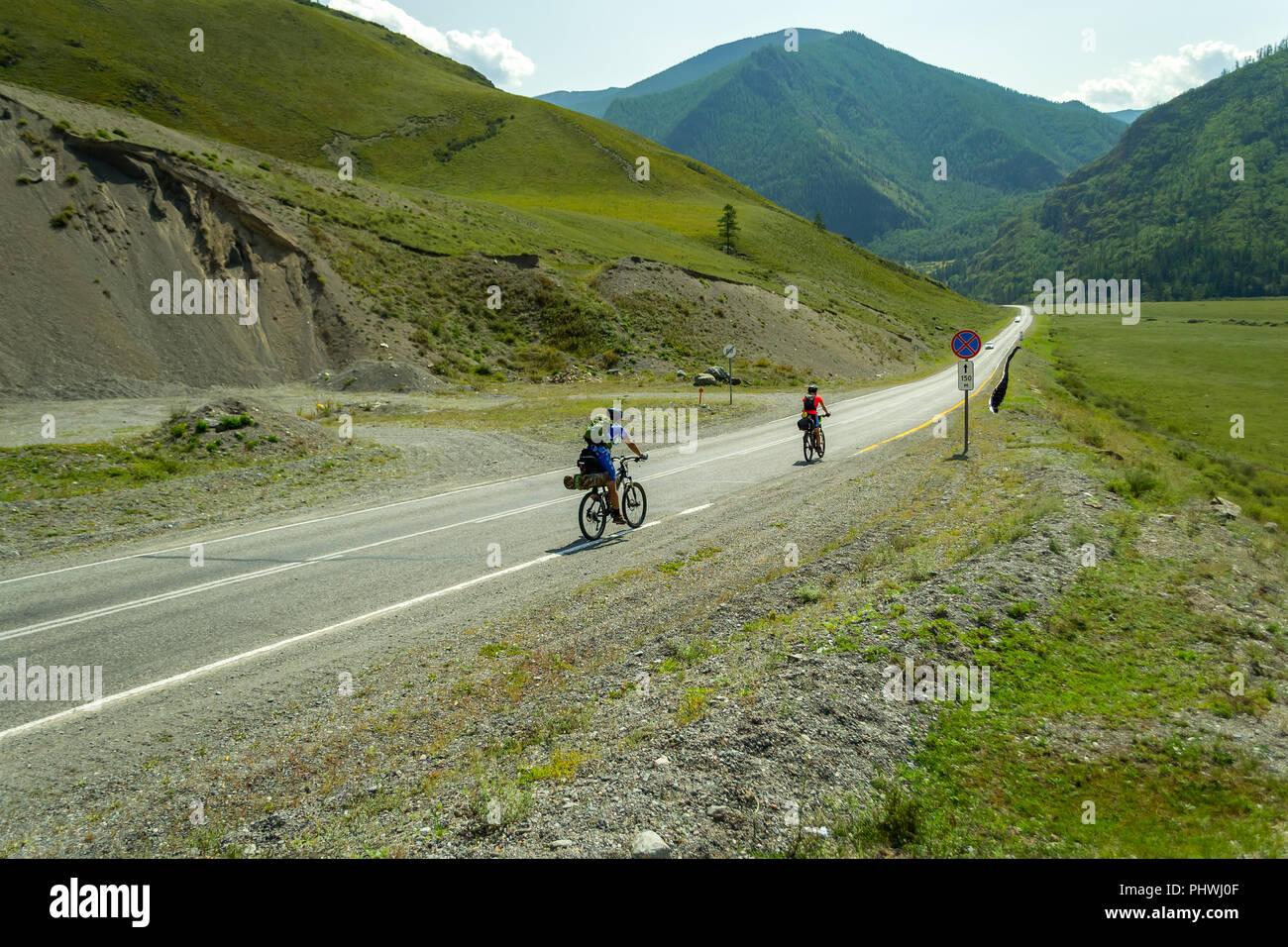 Ein paar der Mann und die Frau in der Helme Fahrt auf Sport Fahrräder auf einer Straße in den Bergen des Altai bis Klettern Stockfoto