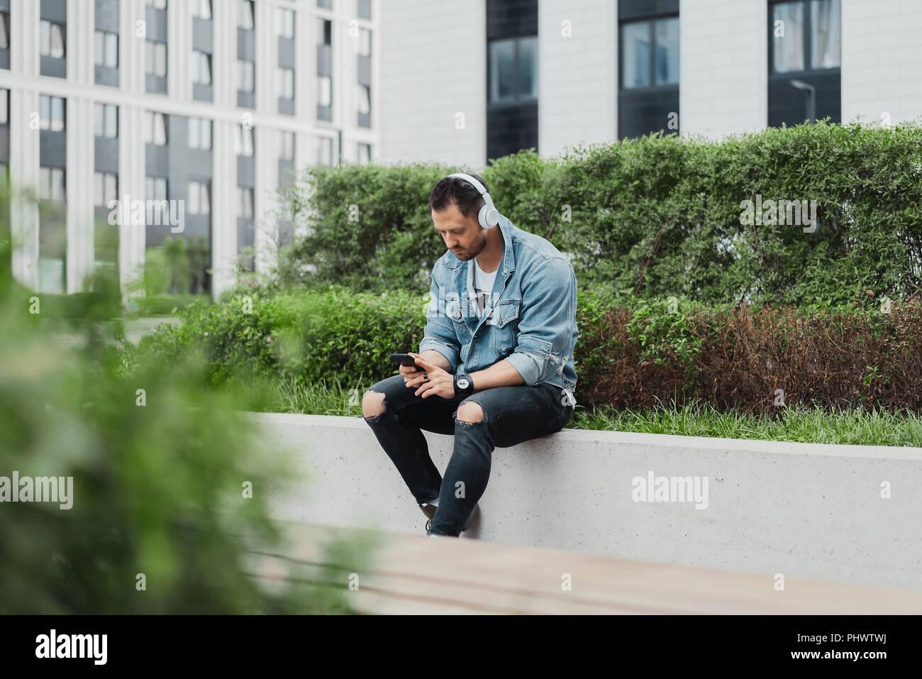 Jungen attraktiven Mann hören die Musik der Ohrhörer im Stadtbild. Stockbild