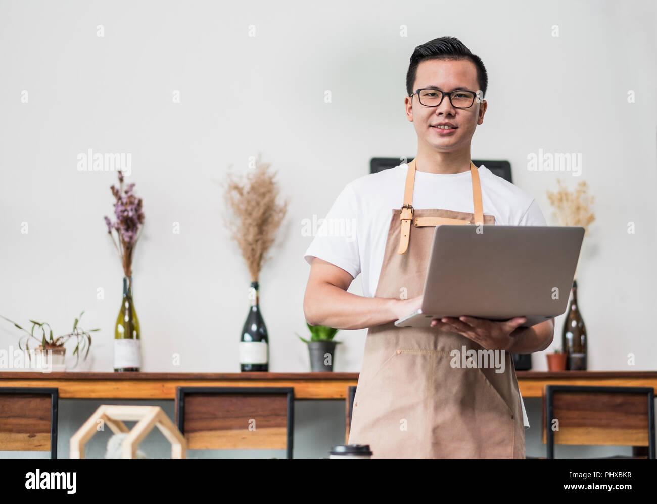Asiatische männlichen Barista Café Eigentümer mit Laptop im Cafe Business im Coffee Shop, schauen und lächeln in die Kamera. Essen und Trinken Geschäft beginnen oben Stockbild