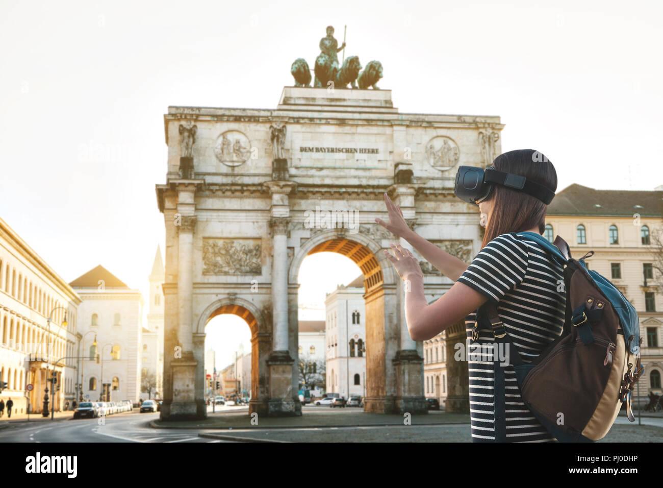 Mädchen Tourist in Gläser der Virtuellen Realität. Virtuelle Reise nach Deutschland. Das Konzept der virtuellen Tourismus. Sightseeing Triumphbogen in München im Hintergrund. Stockbild