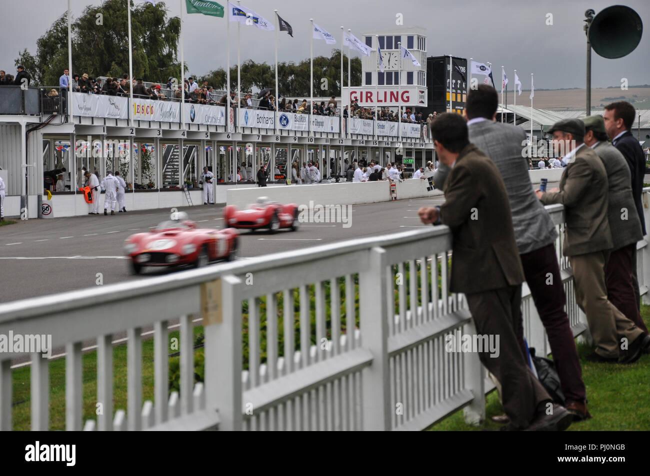 Die Goodwood Revival Die Freddie März Memorial Trophy Rennen, Ausdauer abend Rasse, mit Menschen in Kostümen zu beobachten. Rennwagen Stockbild