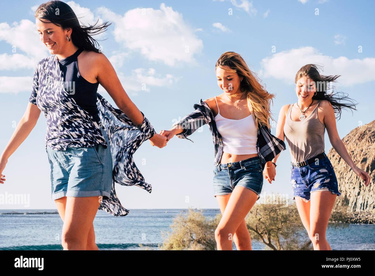 Drei jungen kaukasischen hübsche Mädchen zusammen gehen die Hände einander zu lächeln und zu lachen. Freundliche Konzept der glücklichen Frauen in Outdoor Freizeitaktivitäten ein Stockbild