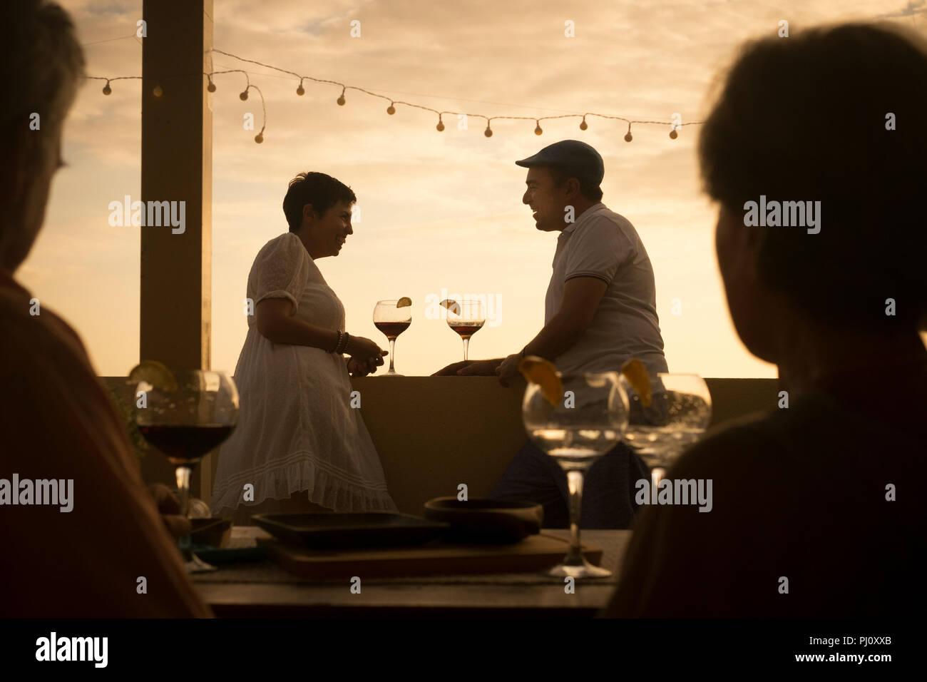 Romantische Szene mit ein paar cacuasian mittleren Alter Menschen trinken einen Cocktail zusammen in Beziehung bei einem bunten gold Sonnenuntergang auf der Terrasse.h Stockbild