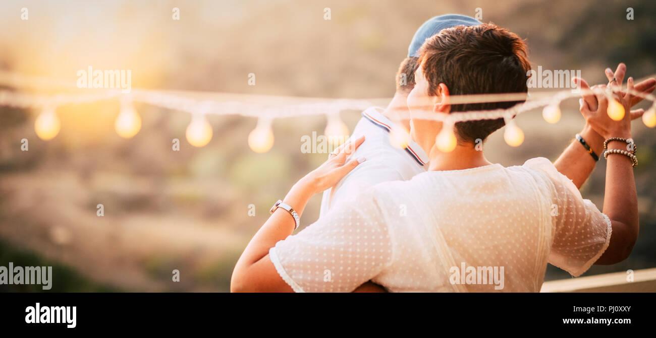 Happy Kaukasier, tanzen zusammen zu Hause in Terrasse mit Leuchten beim Sonnenuntergang. romantisch und Beziehung Konzept Bild für fröhliche Menschen in Stockfoto