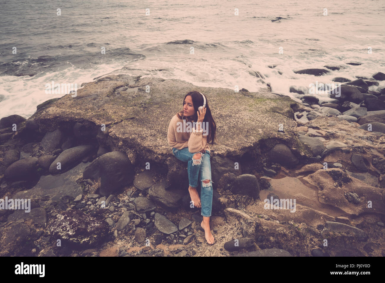 Einsame schöne junge Frau Musik hören und Entspannen mit Meditation und Konzentration sitzen auf einem Felsen mit Blick auf das Meer und den Horizont und niemand in Backgr Stockbild