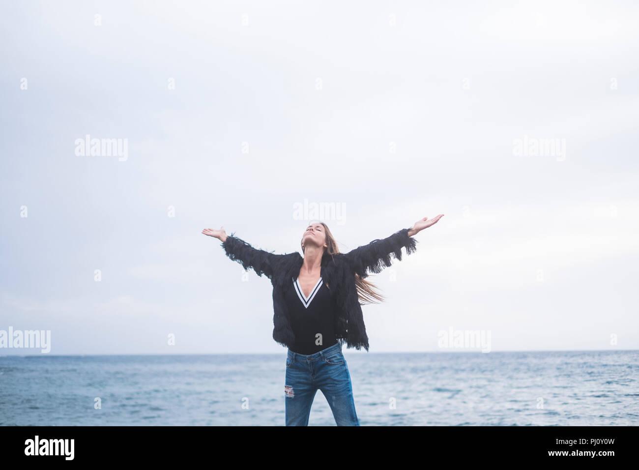 Schöne junge Frau, die auf einem Felsen am Strand den Himmel schauen und genießen Sie die Kraft der Natur und das Gefühl der Freiheit und die Reise. Stockbild