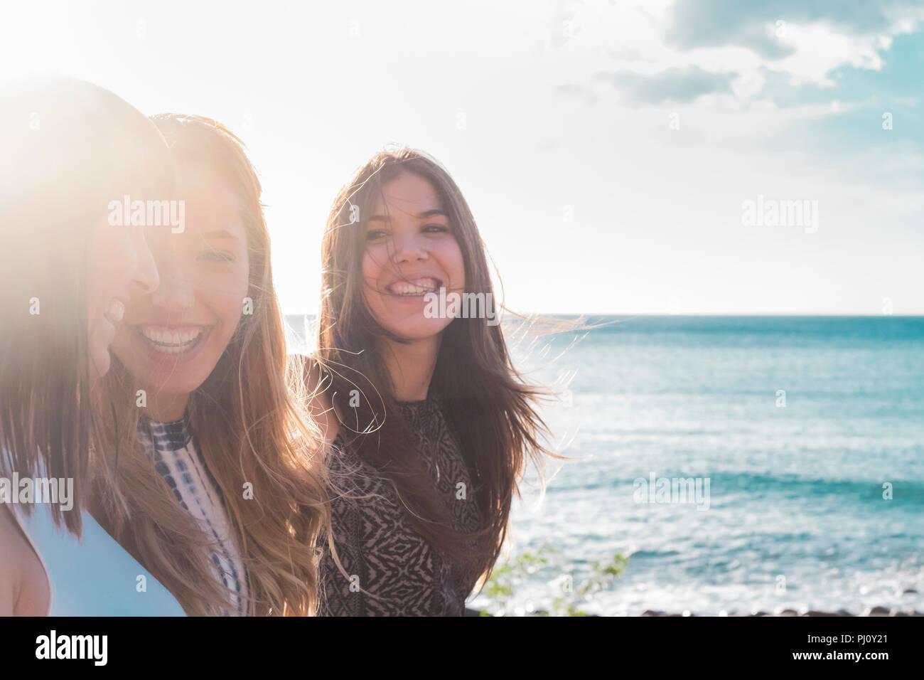 3 Junge Frauen am Strand spazieren gehen, sich gegenseitig suchen, Lachen und freie Zeit zusammen verbringen. an einem schönen Sommertag. mit Sonne und Meer als backgroun Stockbild
