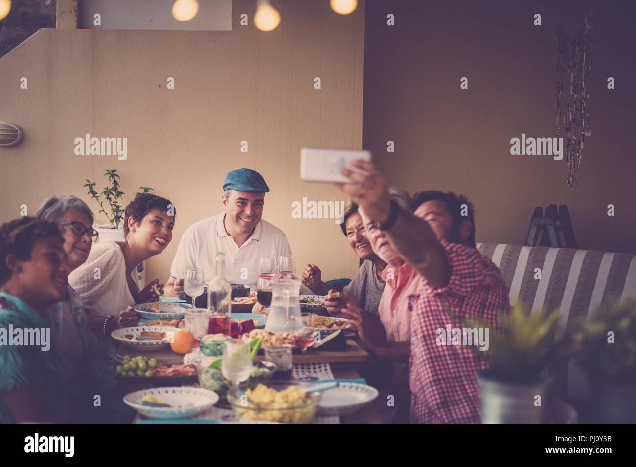 Happy Gruppe von Personen in der Familie Freundschaft alle zusammen feiern und ein schönes Abendessen zu Hause im Freien auf der Terrasse. Ein Mann nehmen selfie für al Stockbild