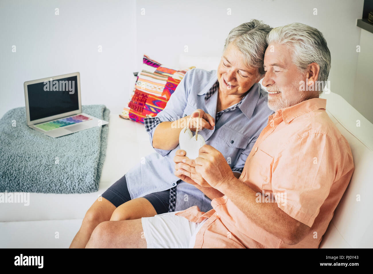 Gerne älterer Erwachsener Paar cacuasian Menschen in Liebe zu Hause sitzen auf dem Sofa und ein Holz handgefertigt Hearth auf Händen. Glück und Fröhlichen Stockbild
