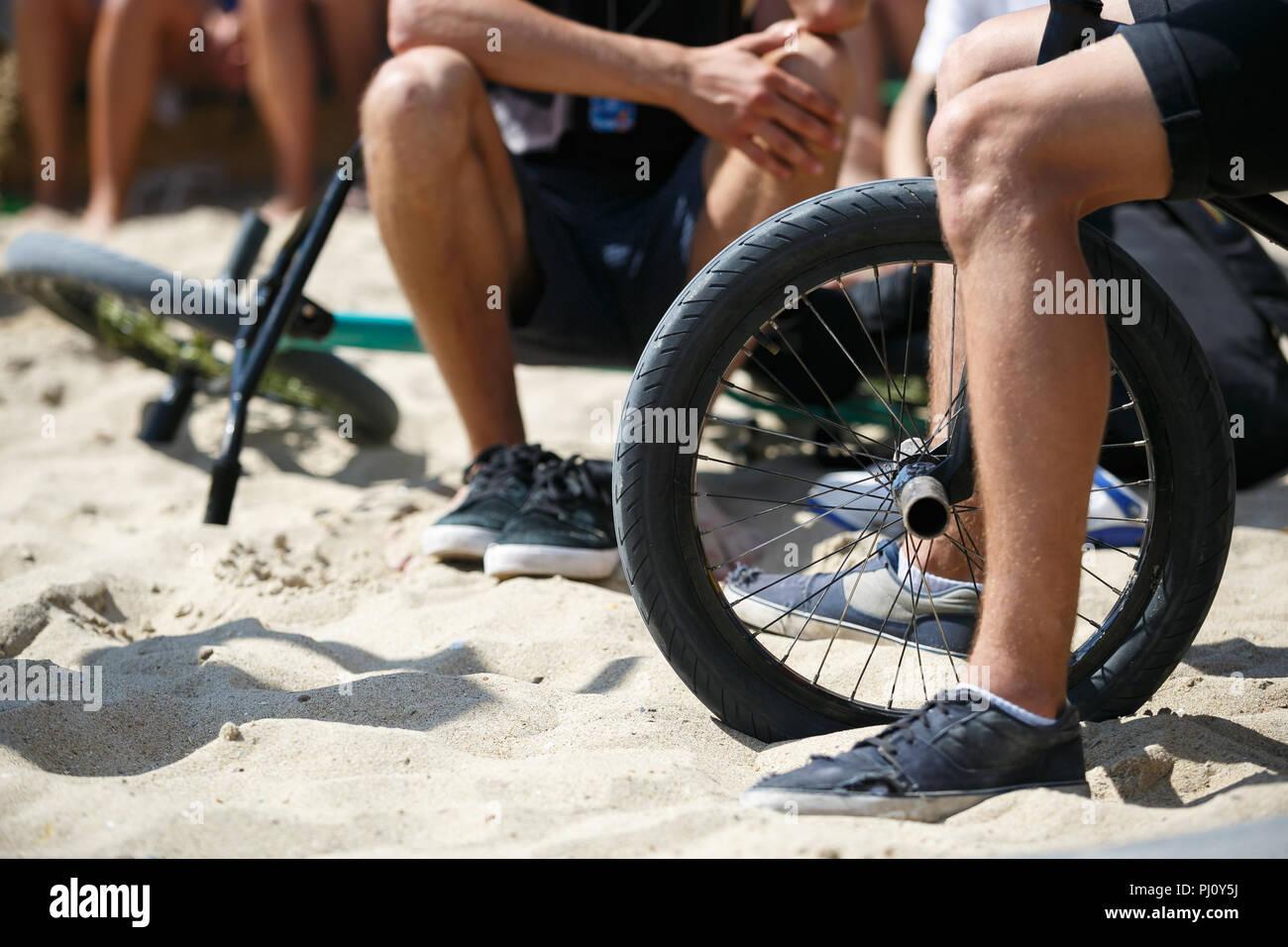 Junge BMX-Fahrer sitzen auf dem Fahrrad in outdoor Park im Sommer extreme sports Festival. Teenager Junge reitet auf spezialisierten Bike zum Ausführen von Tricks in Stockfoto