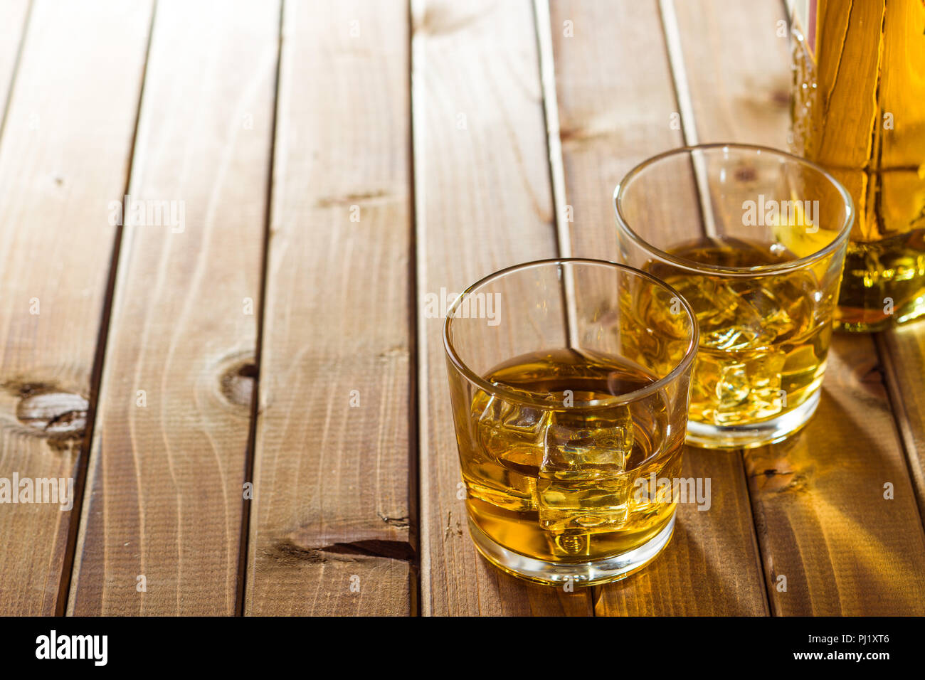 Glas alkoholische Getränke mit Eiswürfeln auf hölzernen Tisch. Whiskey in Glas. Stockbild