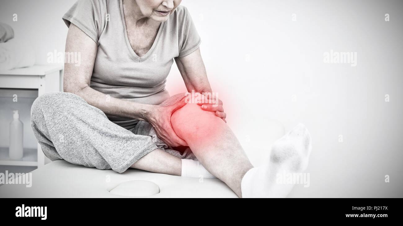 Das zusammengesetzte Bild der älteren Frau mit ihren Händen auf eine schmerzhafte Knie Stockbild