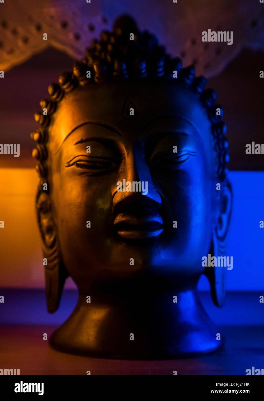 Schwarze Büste Skulptur Buddha in Blau und Orange beleuchtet Stockbild