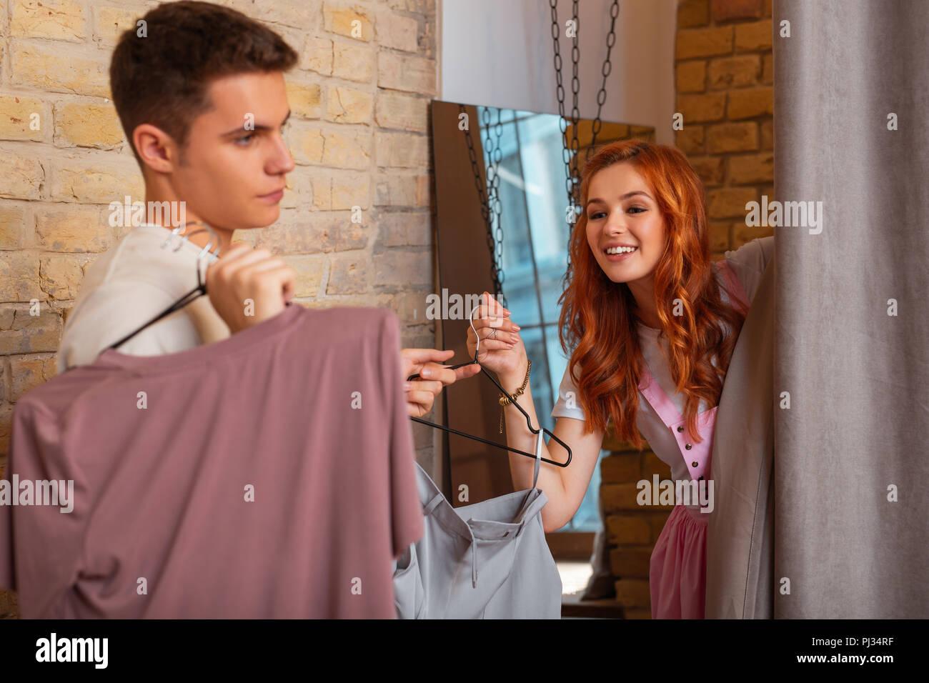 Fröhliches Mädchen, die versuchen, auf der Kleidung und ihr Freund gelangweilt Stockfoto