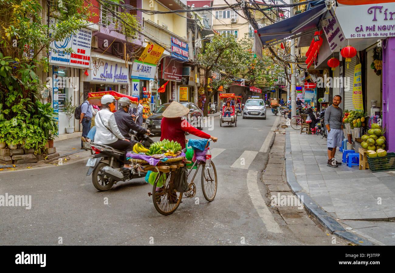 Typische Szene in der Altstadt mit Licht Verkehr und ein Tourist auf der Seite gehen. Editorial, Mar 26, 2017. Hanoi Street Ecke. Stockfoto