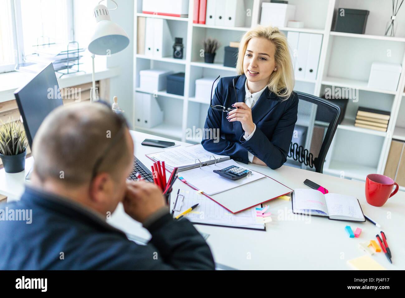 Ein junges Mädchen sitzt an einem Tisch im Büro, die Gläser in der Hand und im Gespräch mit einem Mann. Stockbild