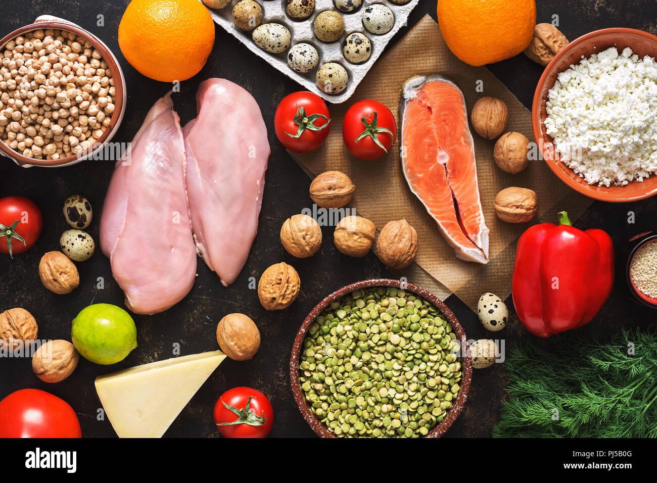 Ausgewogene diätetische Erzeugnisse. Das Konzept der gesunden Ernährung. Hintergrund einer gesunden Mahlzeit. Obst, Gemüse, Lachs, Hähnchenbrustfilet, Getreide. Der Blick von oben, flach. Stockbild