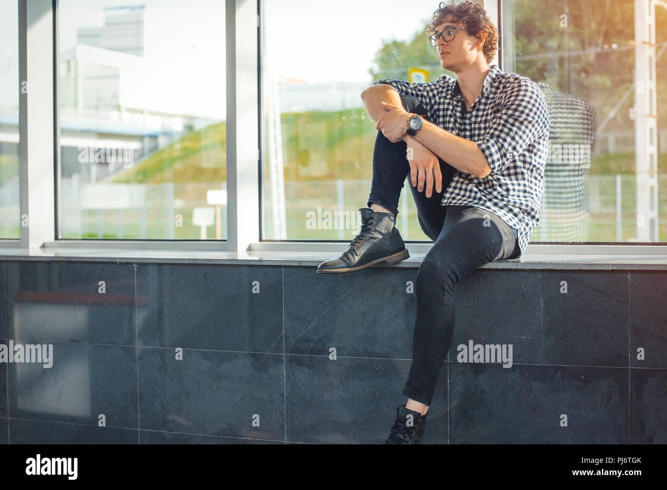 Ferner Plan der junge Mann neben großen Fenstern sitzen an der Metrostation. Stockbild