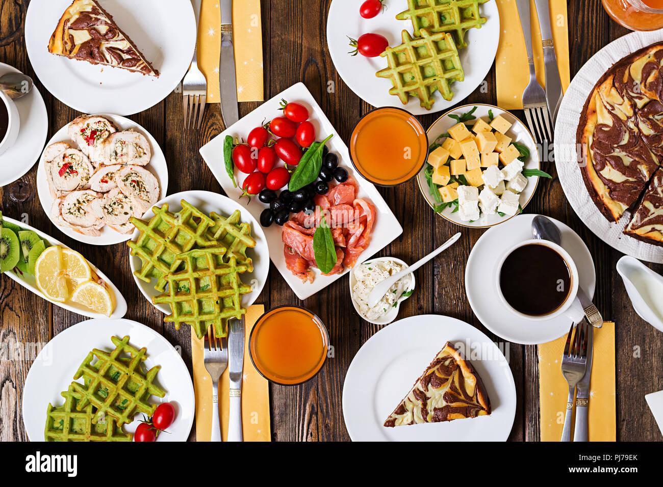 Frühstück in der Tabelle. Festlicher brunch, essen Vielzahl mit Spinat Waffeln, Lachs, Käse, Oliven, chicken Rolls und Käsekuchen. Ansicht von oben. Flach Stockbild