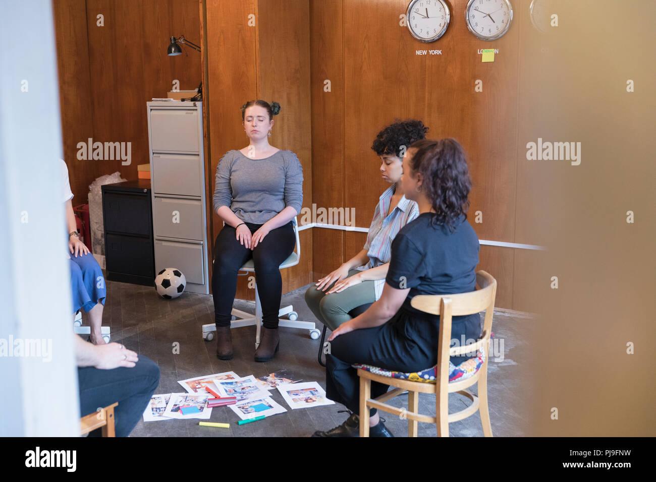 Heitere und kreative Unternehmerinnen meditieren im Kreis, eine Pause in der Sitzung Stockbild
