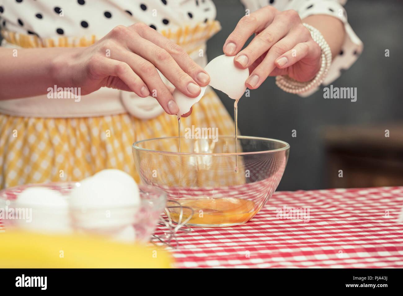 7/8 Schuß von Hausfrau in Polka Dot Shirt, das Ei in die Schüssel für Omelette Stockbild