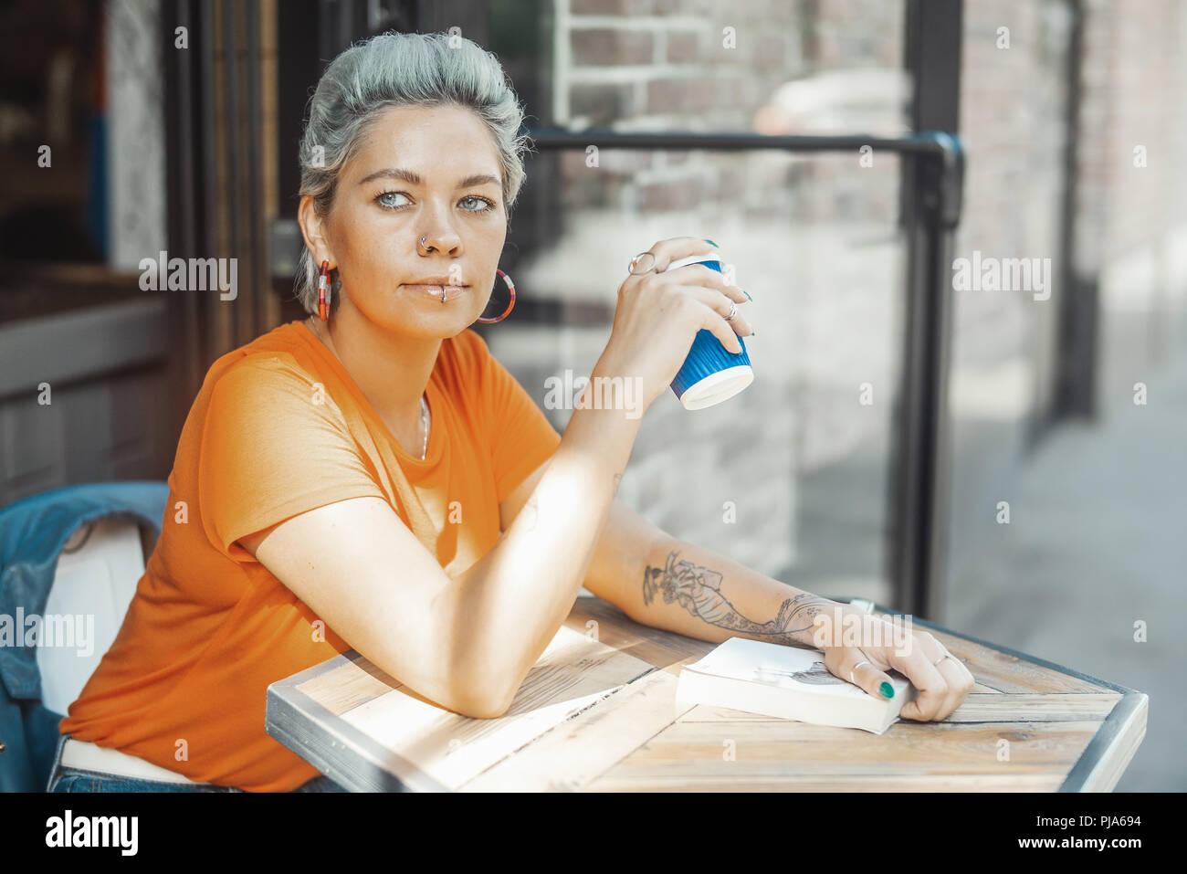 Attraktive junge blonde Mädchen, dass Buch und trinken Kaffee an Street Cafe Stockbild