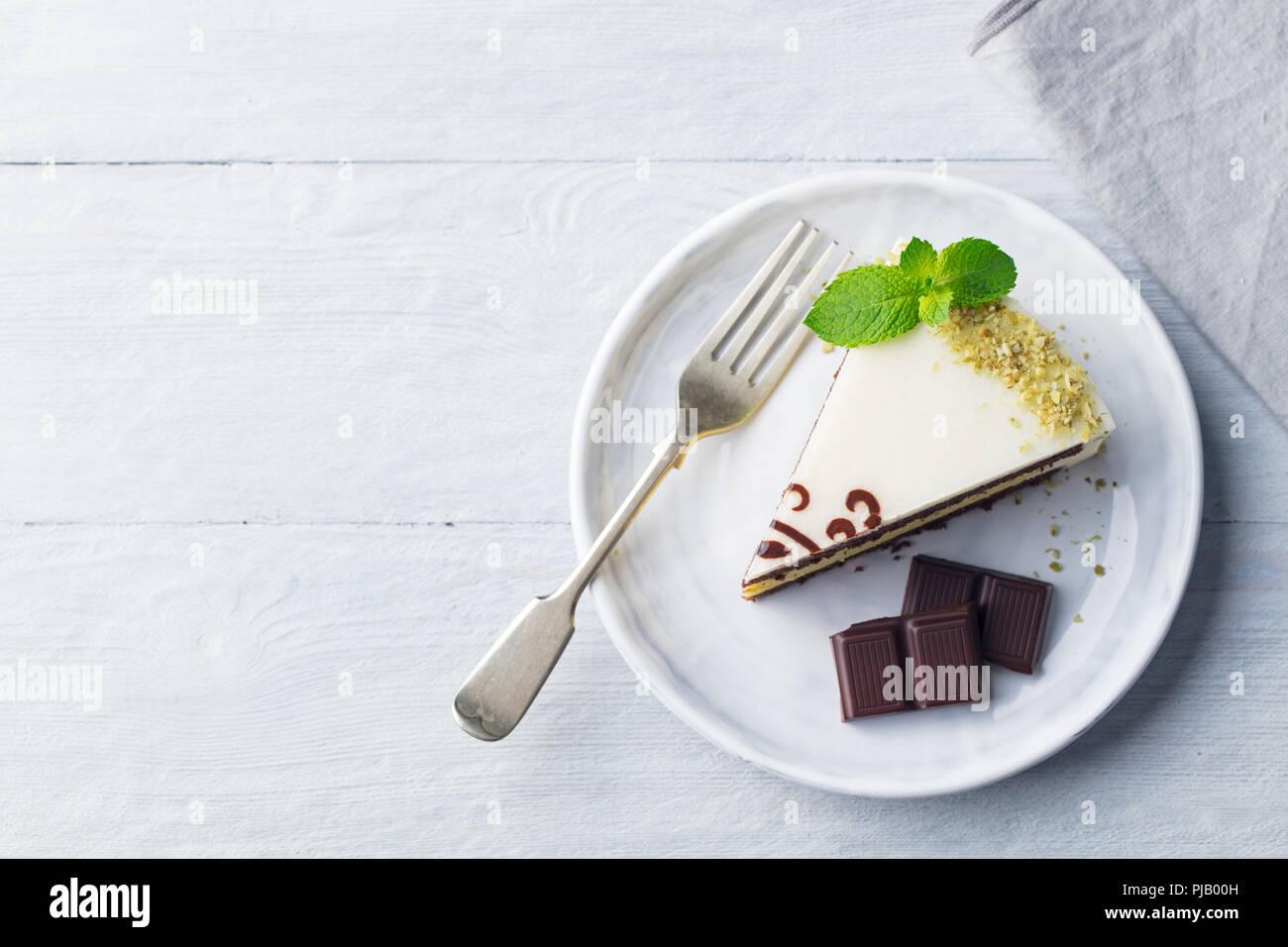 Weiße Schokolade Kuchen mit frischer Minze Lamelle auf einer Platte. Holz- Hintergrund. Kopieren Sie Platz. Top vew. Stockbild