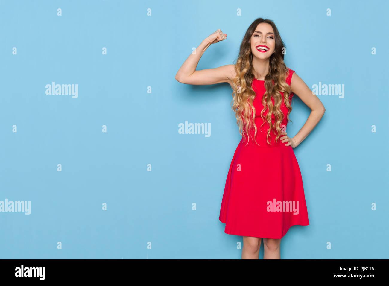 eca0d5d8641c2 Gerne schöne junge Frau im roten Kleid hält den Arm hob, lächelnd ...