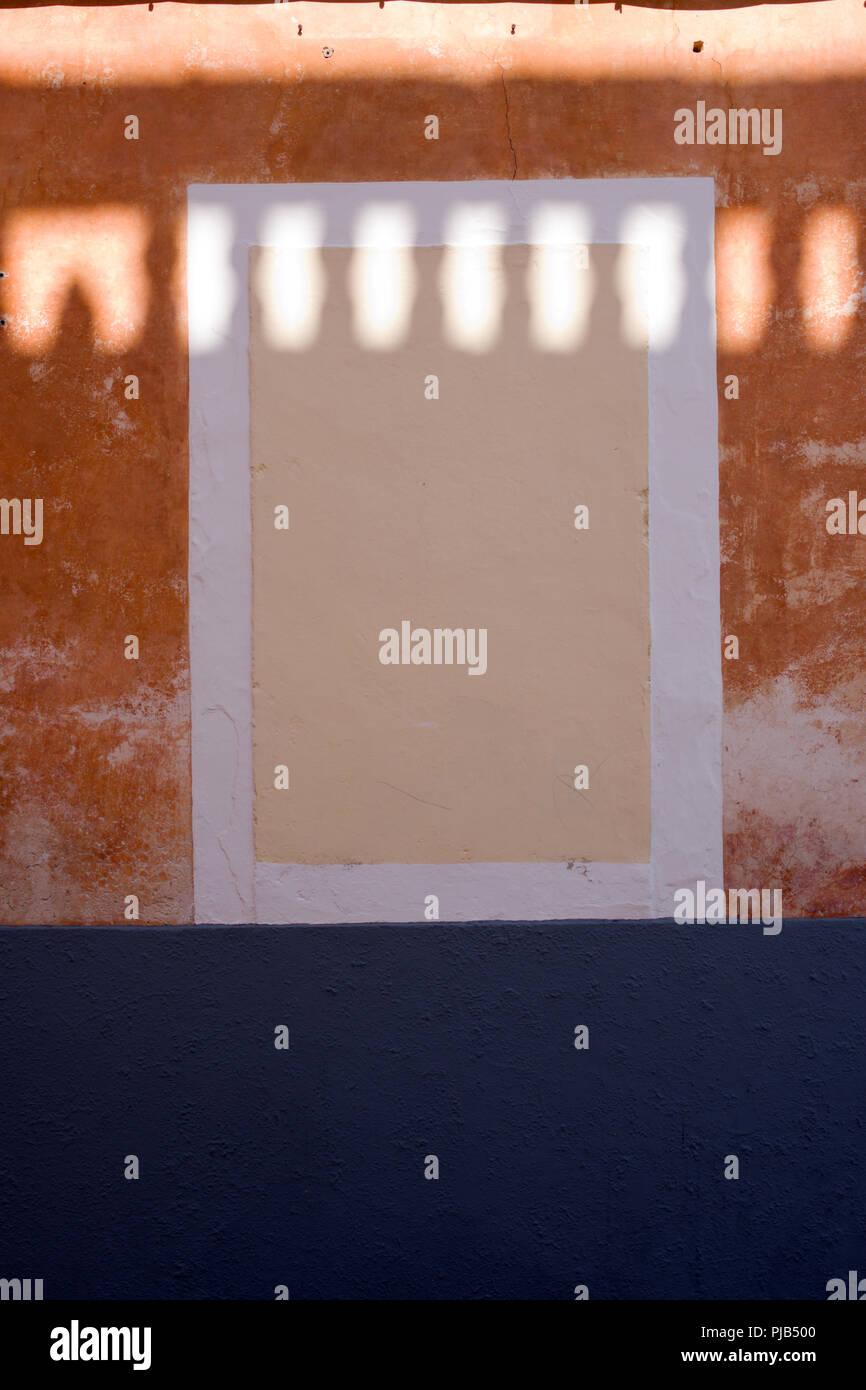 Eindrucksvolle Aufnahme von Licht erzeugen von Mustern mit Schatten auf einer schön texturierte Wand und gemauertem in Fenster in Menorca, Spanien Stockbild