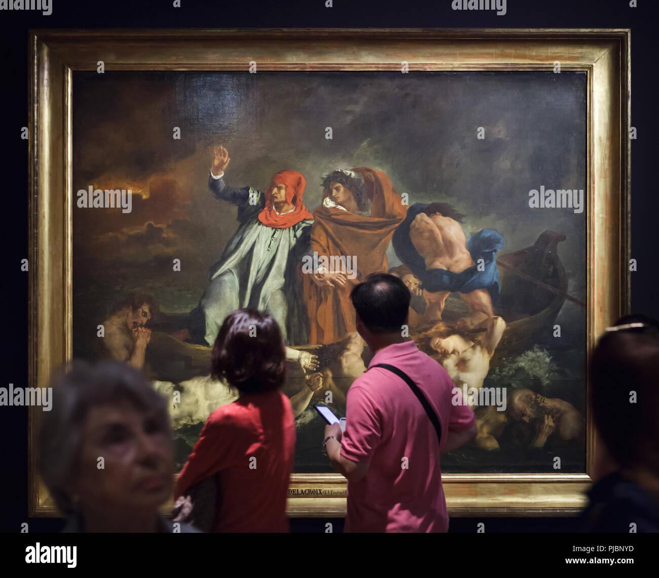 """Besucher vor dem Gemälde """"Der Barke des Dante', das auch als 'Dante und Vergil in der Hölle' durch Französische romantische Maler Eugène Delacroix (1822) bei seiner Retrospektive im Musée du Louvre in Paris, Frankreich angezeigt. Die Ausstellung, die Meisterwerke der Führer der französischen Romantik läuft bis 23. Juli 2018. Stockbild"""