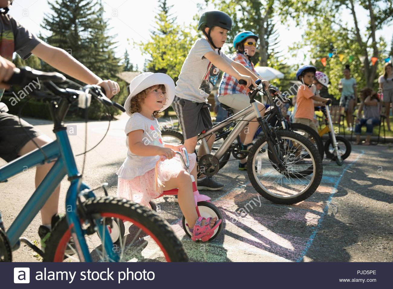 Kinder auf Fahrrädern für Rennen bereit an der Startlinie am Sommer, der Nachbarschaft Block Party Stockbild
