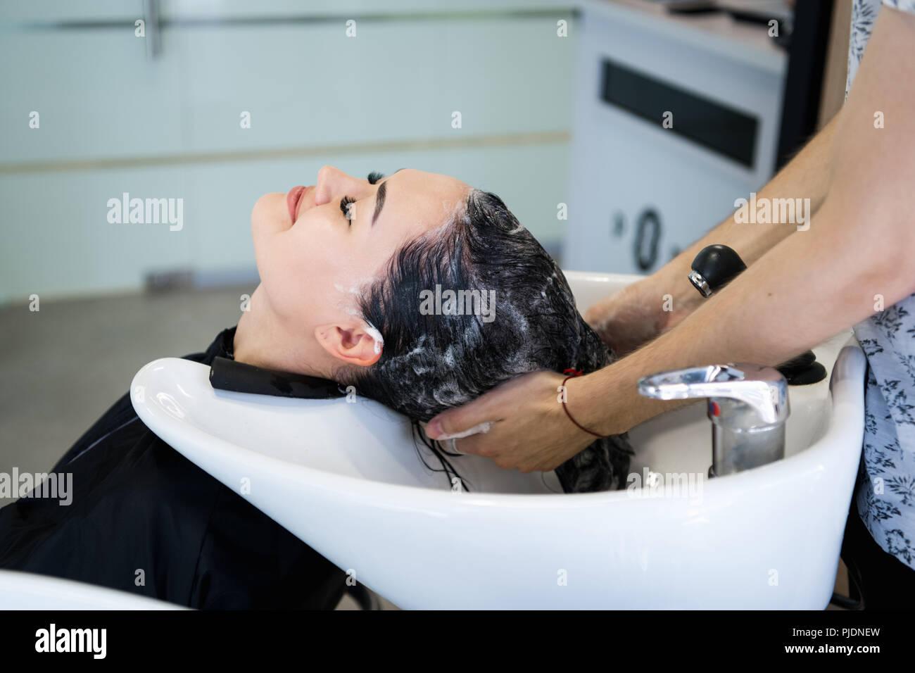 Schöne brünette Mädchen waschen Sie Ihr Haar in der Friseur Stockbild