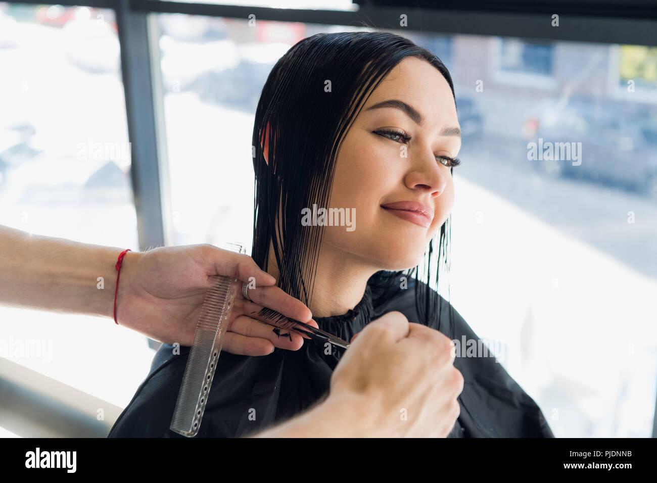 Männliche Friseur einen Haarschnitt für eine schöne Brünette Mädchen im professionellen Friseursalon. Stockbild