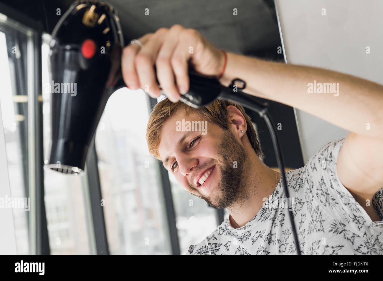 Männliche Friseur lächelnd und im Gespräch mit einem Kunden und gleichzeitig einen neuen Haarschnitt wunderschöne junge brünette Frau Stockbild